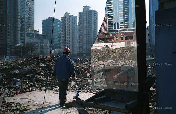 A laborer walks through a demolished old neighborhood that is planned for redevelopment in Shanghai, China in 26 December, 2008.  .Many parts of the city's old neighborhood have been knocked down to erect new high rises, while the city becomes one of the most expensive places in China to live as housing costs sky rocket..