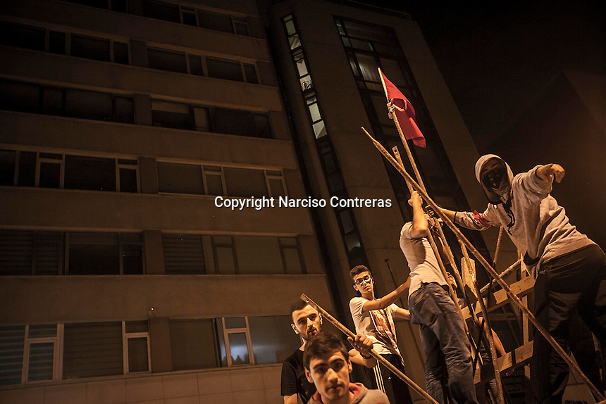 Protesters set up a turkish flag as they reinforce the barricades while expecting new clashes at night with the anti-riot police at the streets nearby Taksim Square during a masive rally against the turkish government in Istanbul, Turkey.