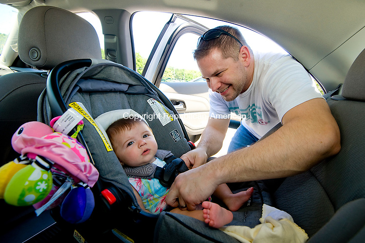 NAUGATUCK, CT-0713017JS01-- Dan Kelly of Naugatuck, secures his six-month-old daughter Addilyn Grace Kelly, into her car seat at the Big Y in Naugatuck on Sunday. <br /> Jim Shannon Republican-American