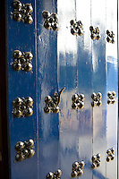 A detail of a brass key in a wooden door studded with a flower motif