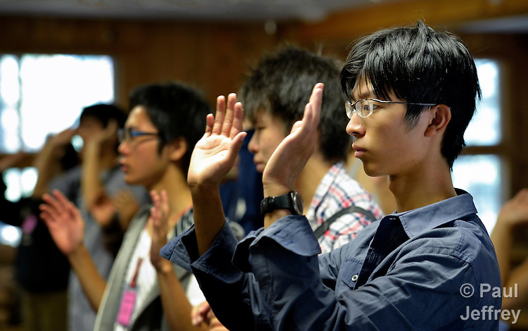 Three Japanese boys raise their arms as they participate in worship during the 2013 Asian American Camp for United Methodist youth, held at Camp Sierra in Big Creek, California. The three boys, along with three girls, came to the camp from the Fukushima region of Japan, site of the nuclear power plant which has spilled radiation since a 2011 earthquake and reactor failure.