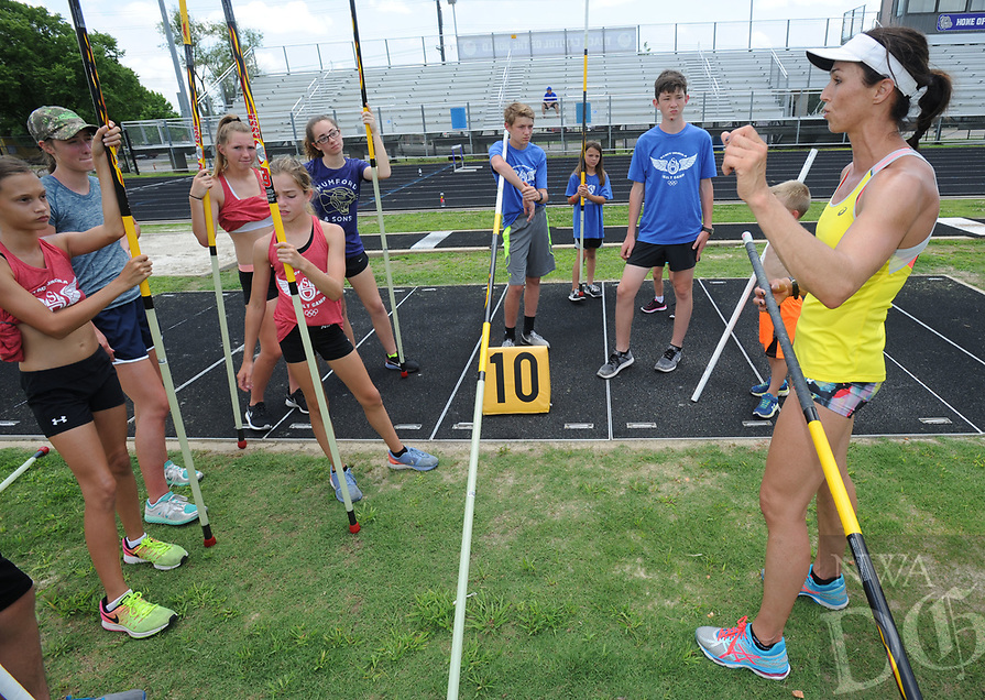 NWA Democrat-Gazette/ANDY SHUPE<br /> April Steiner Bennett (right), a former Arkansas and Olympic pole vaulter, works with campers Friday, June 16, 2017, during instruction for pole vaulters at Ramay Junior High School in Fayetteville. Steiner Bennett and Stacy Dragila, a former Olympic pole vaulter and 2000 Olympic gold medalist, were on hand for two days of intensive instruction for vaulters from elementary to high school.