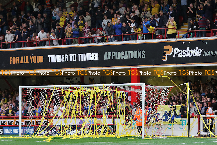Oxford fans throw yellow streamers onto the Brentford goal and let off a flare at the back of the stand during Brentford vs Oxford United, Capital One Cup 1st Round Football at Griffin Park, London, England on 11/08/2015