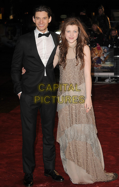 "BEN BARNES & GEORGIE HENLEY.The Royal Film Performance 2010: The World Premiere of ""Chronicles of Narnia: The Voyage of the Dawn Treader"" at the Odeon, Leicester Square, London, England..November 30th 2010.full length tuxedo tux grey gray beige tiered layered lave dress maxi peep toe shoes black bow tie  .CAP/BEL.©Tom Belcher/Capital Pictures."