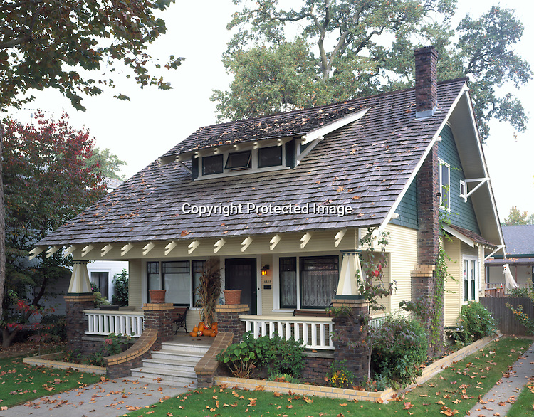 Bungalow in Sacramento, California. With a fringe of shaped rafter tails overhanging its porch and dormer,  this 1911 house looks like it stepped off the pages of a bungalow plan book. Creating a variety of textures, both clinker and buff-colored brick complement the shingled and clapboard siding. An English carpenter named Jennings constructed it over several years, leaving behind a detailed journal of every building expense as a documentary record for the subsequent owners. A large oak tree has grown from one that Mr. Jennings, and his newly arrived bride from England, planted when their son was born. The same son still lives up the street, and has provided the current owners with a generous supply of house and family lore