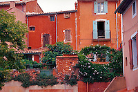 The exterior facade of colorful French buildings constructed with ochre stucco. Rousillon, France.