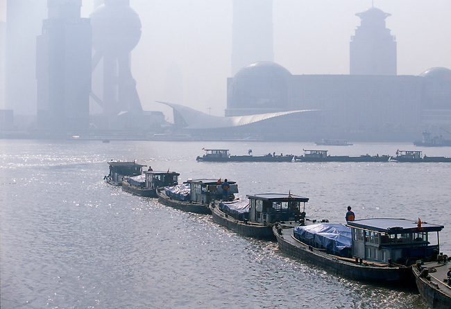 Lines of barges travelling down the Huangpu River on a hazy morning in Shanghai China