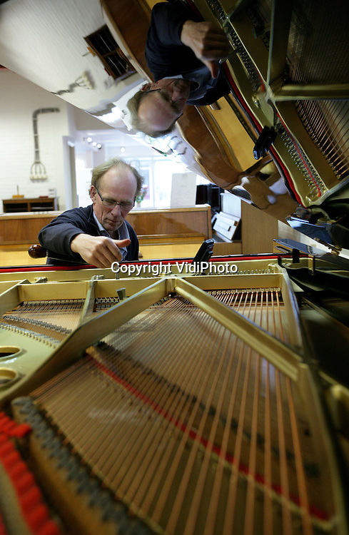 Foto: VidiPhoto..RANDWIJK - Nederlandse pianostemmers komen op dit moment handen te kort. Door de strenge vorst van de afgelopen weken in combinatie met het 'warm en droog stoken' van de woningen, zijn veel piano's ontstemt geraakt of zelfs beschadigd. Stemmen kan pas als de temperaturen weer 'normaal' zijn, zoals nu. Foto: Pianostemmer Leendert van der Waal uit het Betuwse Randwijk woensdag aan het werk.