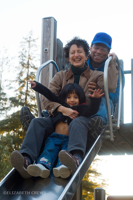 Berkeley CA Parents with adopted Guatemalan girl, three and a half, having fun together on playground slide  MR