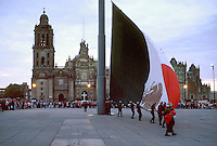 Mexican Army color guard lowers the large national flag that flies in Zocalo Square. Metropolitan Cathedral, Mexico City.