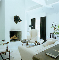 In the living room the tall chimneypiece, which has been given a rendering of rough stucco, and antique furniture add to the rustic atmosphere of the 19th century farmhouse