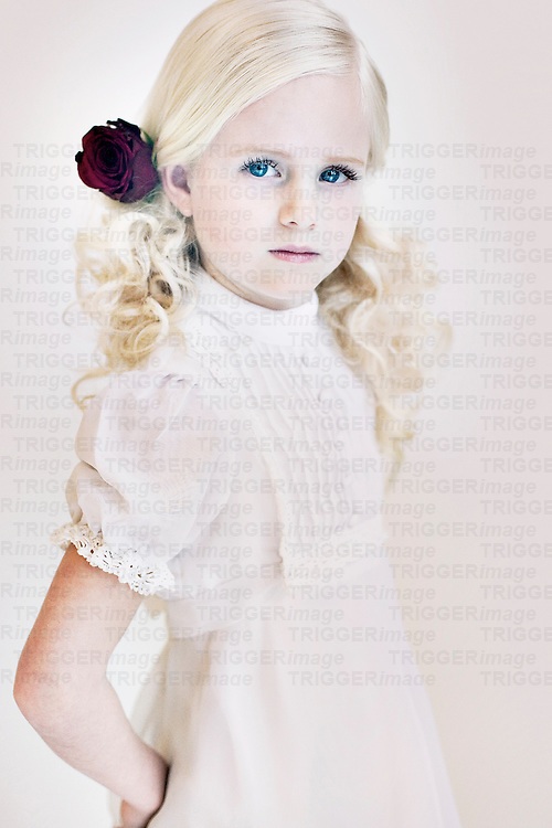 Young girl with purple rose in blonde curly hair wearing white dress looking at camera