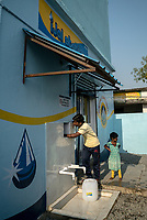 Local residents fill up their cans at the iJal station in Ambedkar Nagar in Medak, Telangana, India.