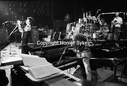 "Paul and Linda McCartney Wings Tour 1975. Rehearsals in Elstree rehearsal studio London, Paul plays the trumpet while Linda is on the keyboard. . The photographs from this set were taken in 1975. I was on tour with them for a children's ""Fact Book"". This book was called, The Facts about a Pop Group Featuring Wings. Introduced by Paul McCartney, published by G.Whizzard. They had recently recorded albums, Wildlife, Red Rose Speedway, Band on the Run and Venus and Mars. I believe it was the English leg of Wings Over the World tour. But as I recall they were promoting,  Band on the Run and Venus and Mars in particular."