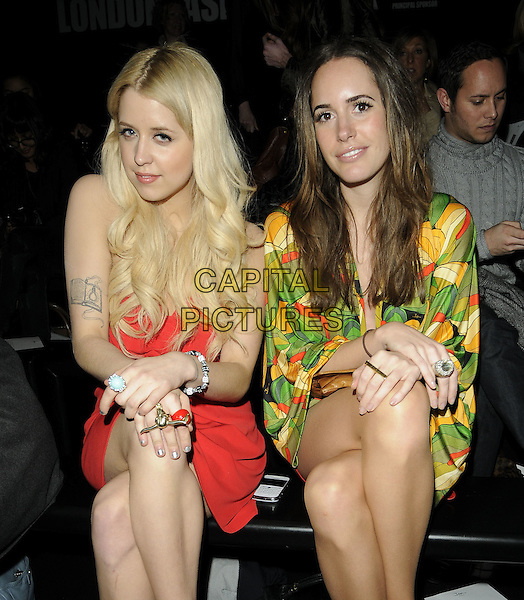 PEACHES GELDOF & LOUISE ROE .At the Issa Fashion Show during London Fashion Week, Somerset House, London, England, UK,.February 23rd 2010..LFW  half length sitting Front Row red dress tattoo black strapless rings green yellow print patterned pattern .CAP/CAN.©Can Nguyen/Capital Pictures.