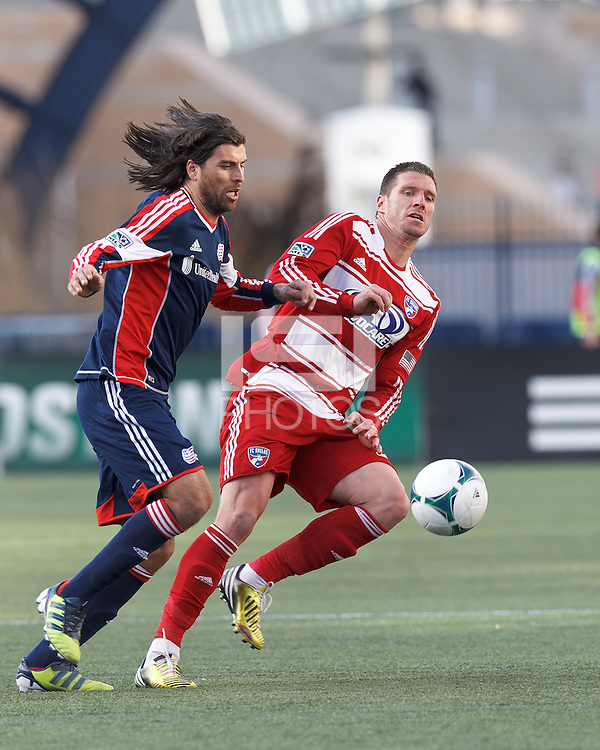 FC Dallas forward Kenny Cooper (33) attempts to control the ball as New England Revolution forward Juan Toja (7) defends..  In a Major League Soccer (MLS) match, FC Dallas (red) defeated the New England Revolution (blue), 1-0, at Gillette Stadium on March 30, 2013.