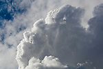 Expanding cumulus strong storm clouds expanding in air below higher cirrus clouds, California