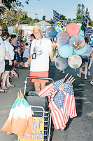A balloon and flag seller works the crowd at the Labor Day parade in Milford, New Hampshire. Republican candidates John Kasich, Carly Fiorina, and Lindsey Graham, and Democratic candidate Bernie Sanders marched in the parade.