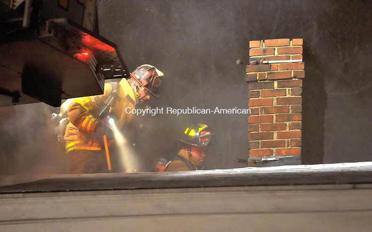 WATERBURY, CT-03 JANUARY 2009-010310JS04- Waterbury firefighters vent the roof around the chimney as they battle a blaze at a home at 337 Lincoln Street in Waterbury Sunday night. The residents and thier two children, along with two dogs, all got out safely. <br /> Jim Shannon Republican-American