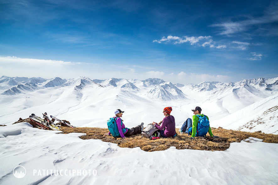 A group of ski tourers sit in dry grass while ski touring in Kyrgyzstan