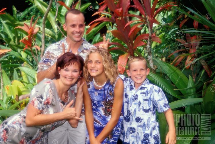 Family in aloha wear pose against lush tropical foliage at Haiku Gardens, windward Oahu.