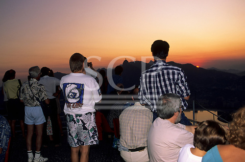 Rio de Janeiro, Brazil. Tourists looking at the Christ statue from the Sugarloaf at sunset.