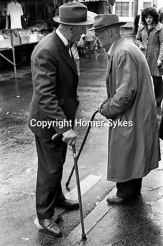 SenUrs with walking sticks and wearing hats, chat in the rain at  Devon 19..Market Day, Holsworthy Devon. 1970s England... My ref 10/1032/, 1975,