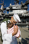 Petty Officer Third Class Gilbert Arambul, a crew member onboard the USS John C. Stennis, holds his three-month-old Natalissa, who was born while he was at sea, after the carrier arrived at Naval Station Kitsap on July 10, 2009 in Bremerton, WA.  The carrier and it's 3,200 crewmembers arrived Friday after spending a six-month deployment in support of  Middle East operations.  (© Jim Bryant Photo. All Rights Reserved