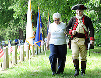 Gertrude Capone, left, is walked with Patrick J. Jordan Jr. after she placed a flag at a gravesite during a gravesite ceremony honoring soldiers who died during Continental Army's December 1776 encampment Sunday May 29, 2016 in Washington Crossing Cemetery in Solebury, Pennsylvania. (Photo by William Thomas Cain)