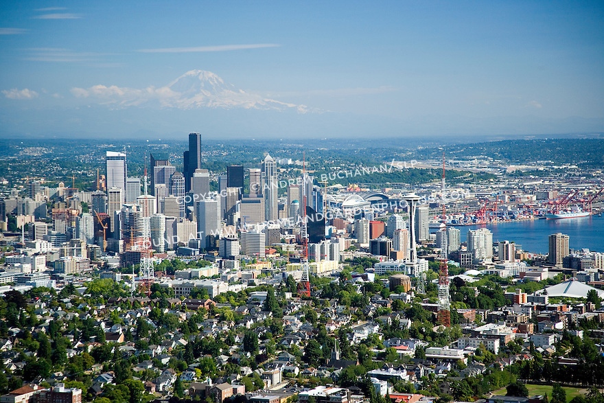 A sunny, summer afternoon aerial photo of Seattle, Washington showing green and leafy Queen Anne Hill in the foreground, the skyscrapers of the downtown skyline and the orange cranes of the Port of Seattle, and snow-capped Mount Rainier towering in the distance in this classic image of a modern Northwest city.