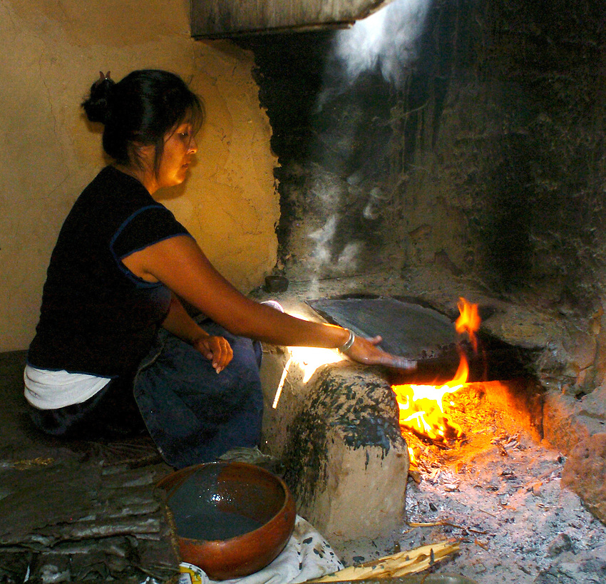 "Annetta Koruh ""Nita"" bakes Piki Bread for her godson's Naming ceremony and to feed the Kachinas that come to dance at 3rd Mesa..   The baker dips their hand in a mixture of cornmeal, crisco, and sheep brains plies.the mixture thinly upon a flagstone rock.which bakes the bread."