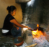 """Annetta Koruh """"Nita"""" bakes Piki Bread for her godson's Naming ceremony and to feed the Kachinas that come to dance at 3rd Mesa..   The baker dips their hand in a mixture of cornmeal, crisco, and sheep brains plies.the mixture thinly upon a flagstone rock.which bakes the bread."""