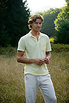 Young man standing in open meadow