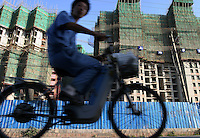 Cyclists ride past rolls of apartment buildings being built in Shanghai, China. Driven by sizzling investment that has fuelled fears of inflation and bad loans, China is struggling to slow an economy that grew 9.8 percent annually for the first quarter of 2004, triggering a slew of measures taken by the coutry's central bank including the halt of all loans made to fixed-asset investment projects not approved by the government..03-JUN-04