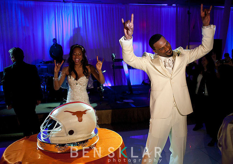 Richards and Ross get their Horns up, saluting the University of Texas, as a football helmet cake with one side the Longhorns and the opposite the New York Giants is presented. Olympic gold medalist, Sanya Richards, and New York Giants cornerback, Aaron Ross, wed at the Hyde Park Baptist in Austin, Texas on Friday, February 26, 2010...