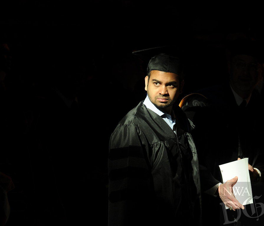 NWA Democrat-Gazette/ANDY SHUPE<br /> Shamin Ahmed, a University of Arkansas engineering doctoral candidate, searches the stands for relatives and friends Saturday, May 13, 2017, during commencement exercises in Bud Walton Arena in Fayetteville. Visit nwadg.com/photos to see more photographs from the ceremony.