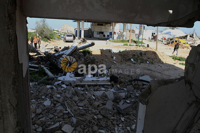 Palestinians walk between rubbles of houses, which were destroyed during the recent Israeli war, in Khuzaa, east of Khan Younis, in the southern Gaza Strip, on March 01, 2015. Photo by Abed Rahim Khatib