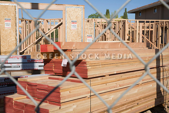 A stack of wood beams and boards sits behind a fence and in front of a wood frame residential home under construction. Building a wood frame house with traditional building methods consumes a large amount of natural resources such as  trees used for lumber.