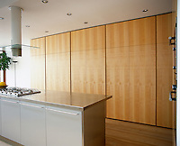 An open plan stainless steel kitchen with floor to ceiling cupboards