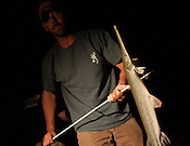 Matt Wroe holds a gar he caught while bowfishing in Aquia Creek, Virginia on June 20, 2013. CREDIT: Lance Rosenfield
