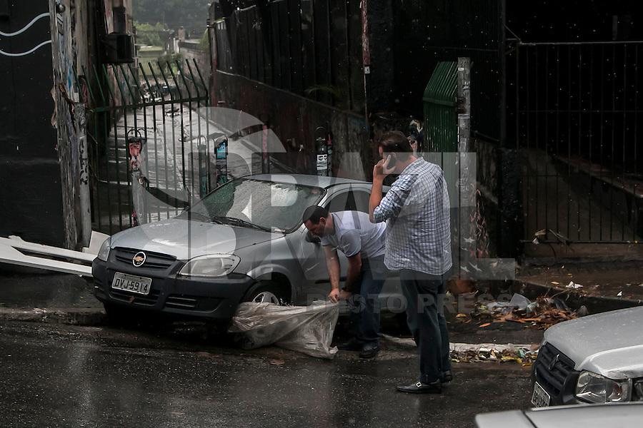 """SÃO PAULO, SP, 19.12.2014 - FORTE CHUVA ATINGE O BAIRRO DA VILA MADALENA - Proprietário avalia os danos causados  em seu veículo devido as fortes chuvas. Uma forte chuva atingiu a região da Rua Harmonia, local onde fica o """"beco do batman, no bairro da Vila Madalena. O local é conhecido pelo histórico de enchentes, na tarde desta sexta - feira (19), na zona oeste de São Paulo. (Foto: Taba Benedicto/ Brazil Photo Press)"""