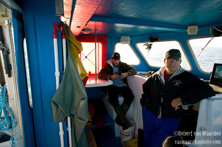 Two fisherman wait for a bite while blue fin tuna fishing on the Gulf of St. Lawrence near North Rustico, Prince Edward Island, Canada.