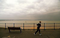 A woman jogs by the sea in Mumbles
