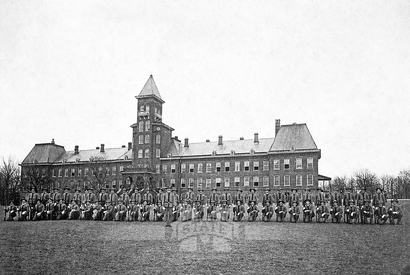 Cadets lined up on the Drill Field in front of the Chapel Building circa 1902. The Chapel Building would later become the base structure of Old Main Dormitory.<br />