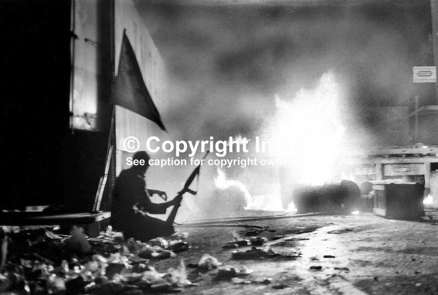 Belfast, N Ireland - Official IRA gunman, Joe  McCann, silhouetted by burning barricade, operating in the Markets Area during anti-internment rioting August 1971. Ref: 197108001.<br />