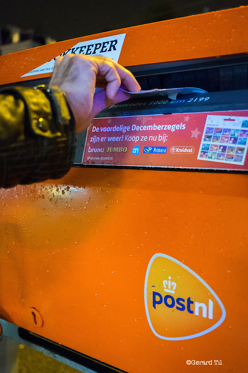 Nederland, Amsterdam,   15-11-2016  Een man post een brief in een oranje postbus van PosNL. Het Belgische Bpost probeert PostNL over te nemen. A man is posting in a letter in an PostNL letterbox. Belgian peer Bpost is atempting to takeover PostNL. FOTO: Til & Wijnbergh / Hollandse Hoogte