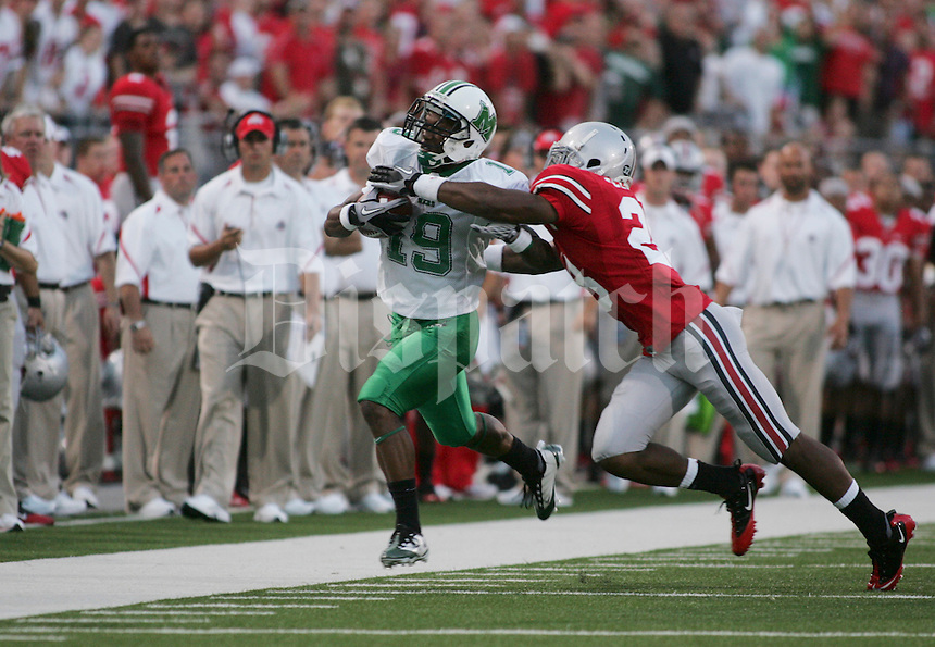 Ohio State defensive back, Dominic Clarke (28) tackles Marshall, running back, Andre Brooker, (19) during the first quarter of the NCAA football game at Ohio Stadium, Thursday, September 2, 2010.(Photo by Courtney Hergesheimer)