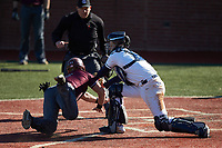 Jakob Divers (2) of the Concord Mountain Lions is tagged out  at home plate by Wingate Bulldogs catcher Logan McNeely (18) at Ron Christopher Stadium on February 2, 2020 in Wingate, North Carolina. The Mountain Lions defeated the Bulldogs 12-11. (Brian Westerholt/Four Seam Images)