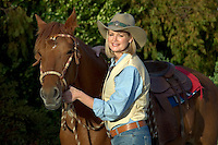 A COWGIRL in vest & jeans with her horse