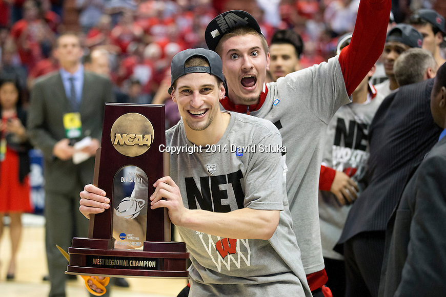 Wisconsin Badgers Ben Brust (1) holds the West Regional trophy after  the Western Regional Final NCAA college basketball tournament game against the Arizona Wildcats Saturday, March 29, 2014 in Anaheim, California. The Badgers won 64-63 (OT). (Photo by David Stluka)